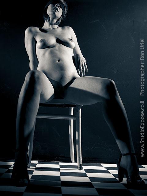 אישה יושבת בעירום בפישוק