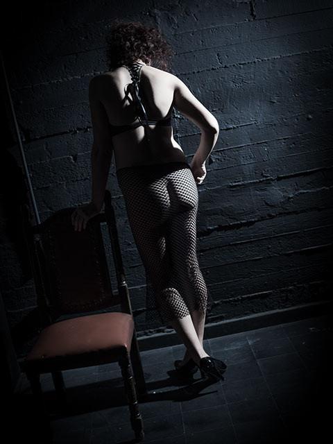 אישה עירומה עומדת. צילום מהגב