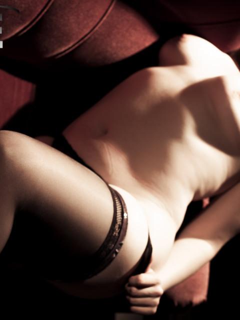 אישה עירומה שוכבת על ספה - צילום עירום אמנותי ארוטי בסטודיו אקספוז